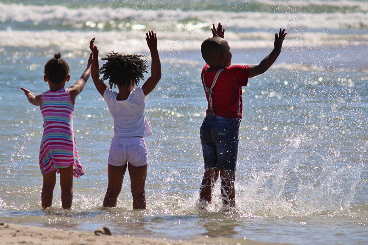 Фотографии девочка Мальчики Дети Негр Море с брызгами три вид сзади Девочки мальчик мальчишки мальчишка ребёнок негры Брызги Сзади Трое 3 втроем