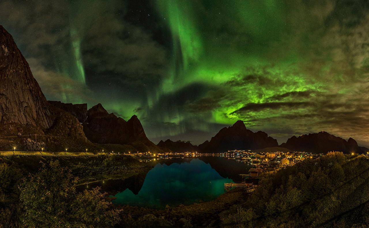 Фотографии Норвегия Reine Полярное сияние Горы Природа Небо Озеро Ночные Облака северное сияние Ночь