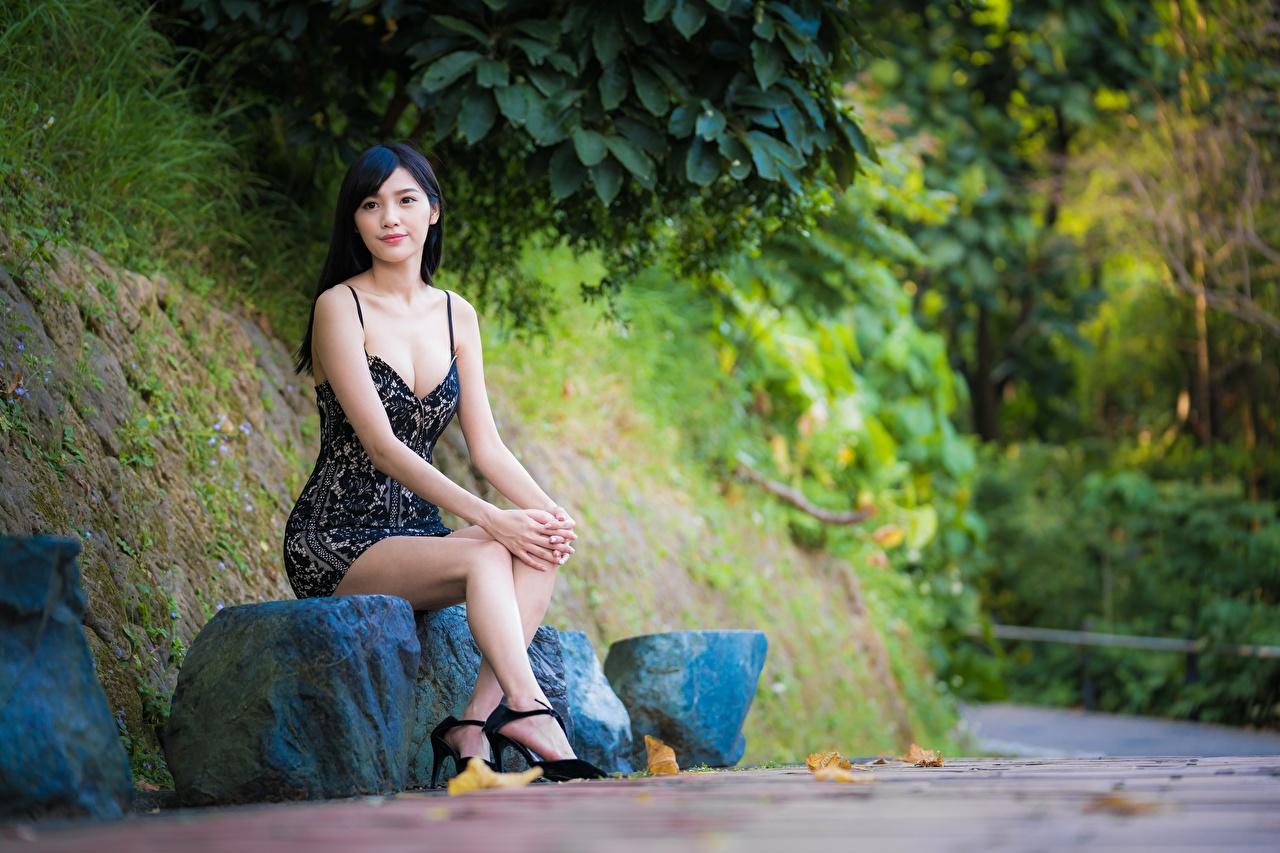 Картинка Брюнетка боке Девушки ног азиатки Сидит Камень платья брюнеток брюнетки Размытый фон девушка молодые женщины молодая женщина Ноги Азиаты азиатка сидя Камни сидящие Платье