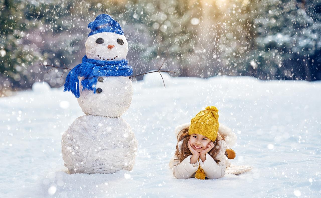 Картинки Девочки Рождество Шарф Улыбка Лежит ребёнок Шапки зимние снега снеговика девочка Новый год шарфе шарфом улыбается лежа лежат лежачие Дети Зима шапка в шапке Снег снегу снеге снеговик Снеговики