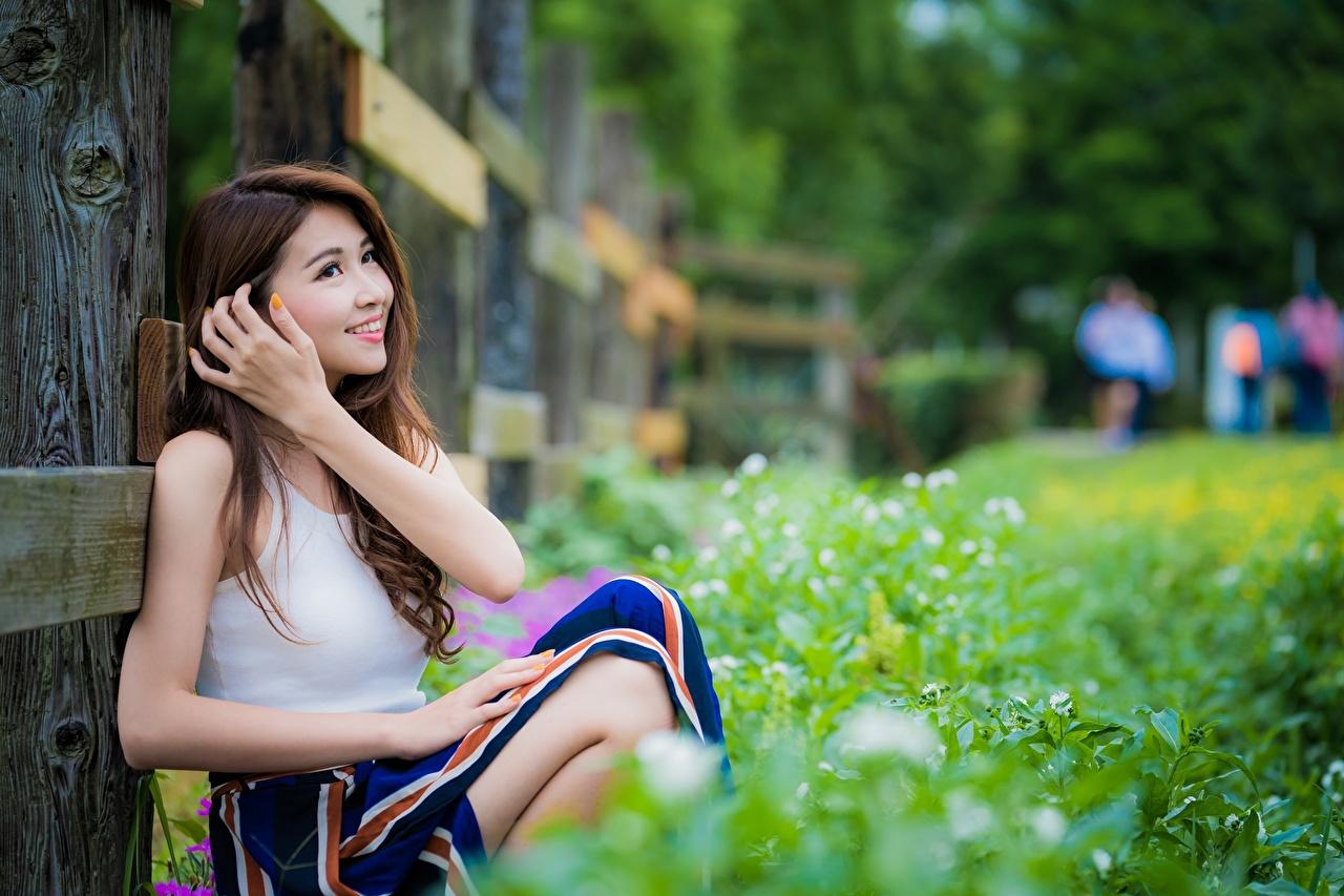 Фото шатенки Улыбка Размытый фон девушка азиатки сидя рука траве Шатенка улыбается боке Девушки молодая женщина молодые женщины Азиаты азиатка Руки Трава Сидит сидящие