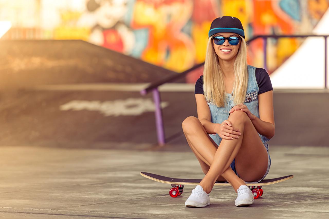 Фото Блондинка улыбается девушка ног Скейтборд Сидит очках Бейсболка блондинок блондинки Улыбка Девушки молодые женщины молодая женщина Ноги Роликовая доска сидя Очки очков сидящие Кепка кепке кепкой