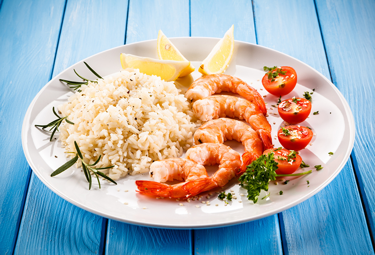 Обои для рабочего стола Рис Помидоры Лимоны Креветки Еда Тарелка Доски Вторые блюда Томаты Пища тарелке Продукты питания