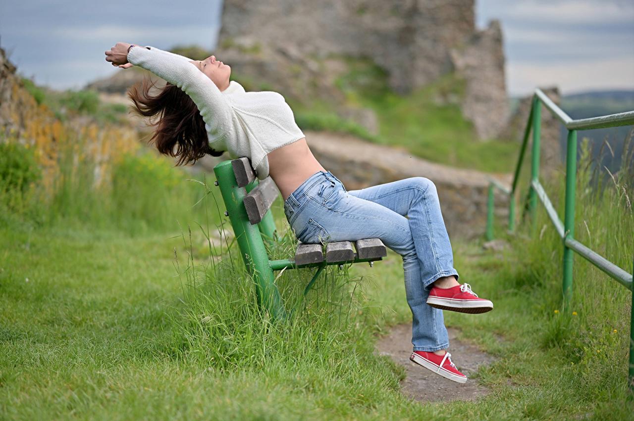 Обои для рабочего стола шатенки Кеды девушка Свитер джинсов траве сидящие Скамейка Шатенка кедах кедами Девушки молодая женщина молодые женщины Джинсы свитере свитера сидя Сидит Трава Скамья
