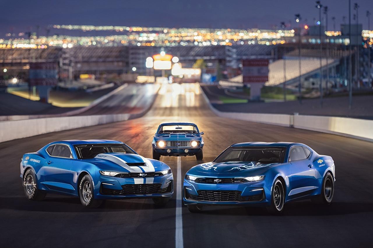 Фотографии Шевроле Camaro 2018 50th Anniversary, COPO, SEMA 2018, eCOPO Concept синяя три машины Chevrolet синих синие Синий авто Трое 3 машина втроем автомобиль Автомобили