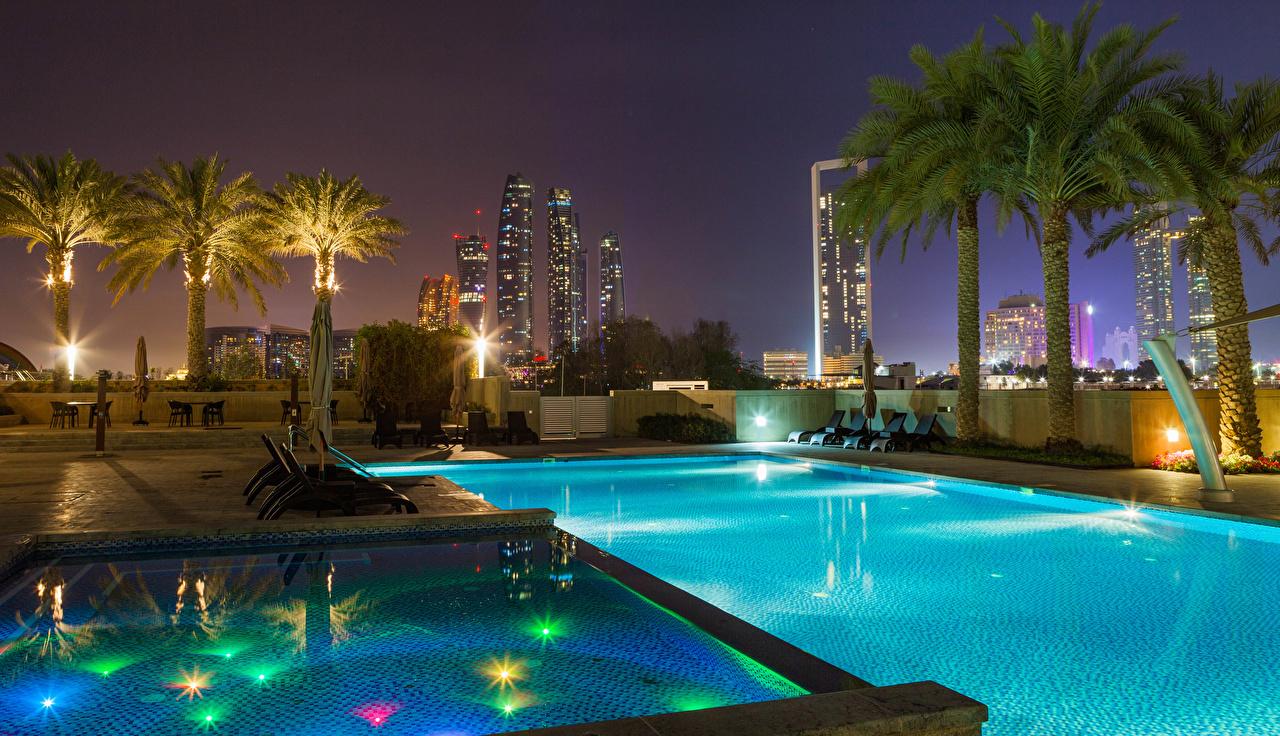 Обои Объединённые Арабские Эмираты Курорты Бассейны Abu Dhabi Пальмы Ночь Города Здания ОАЭ Плавательный бассейн Ночные Дома