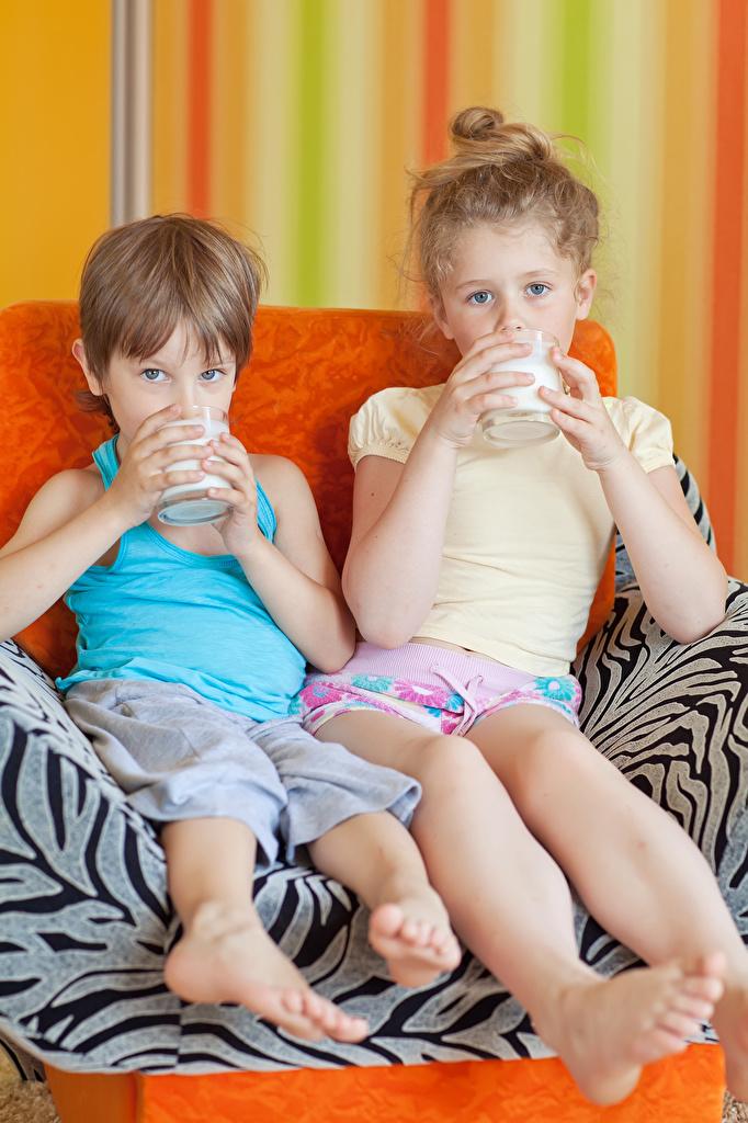 Картинка Молоко Девочки Мальчики Дети Двое Стакан Сидит Взгляд Ребёнок 2 вдвоем сидящие смотрит