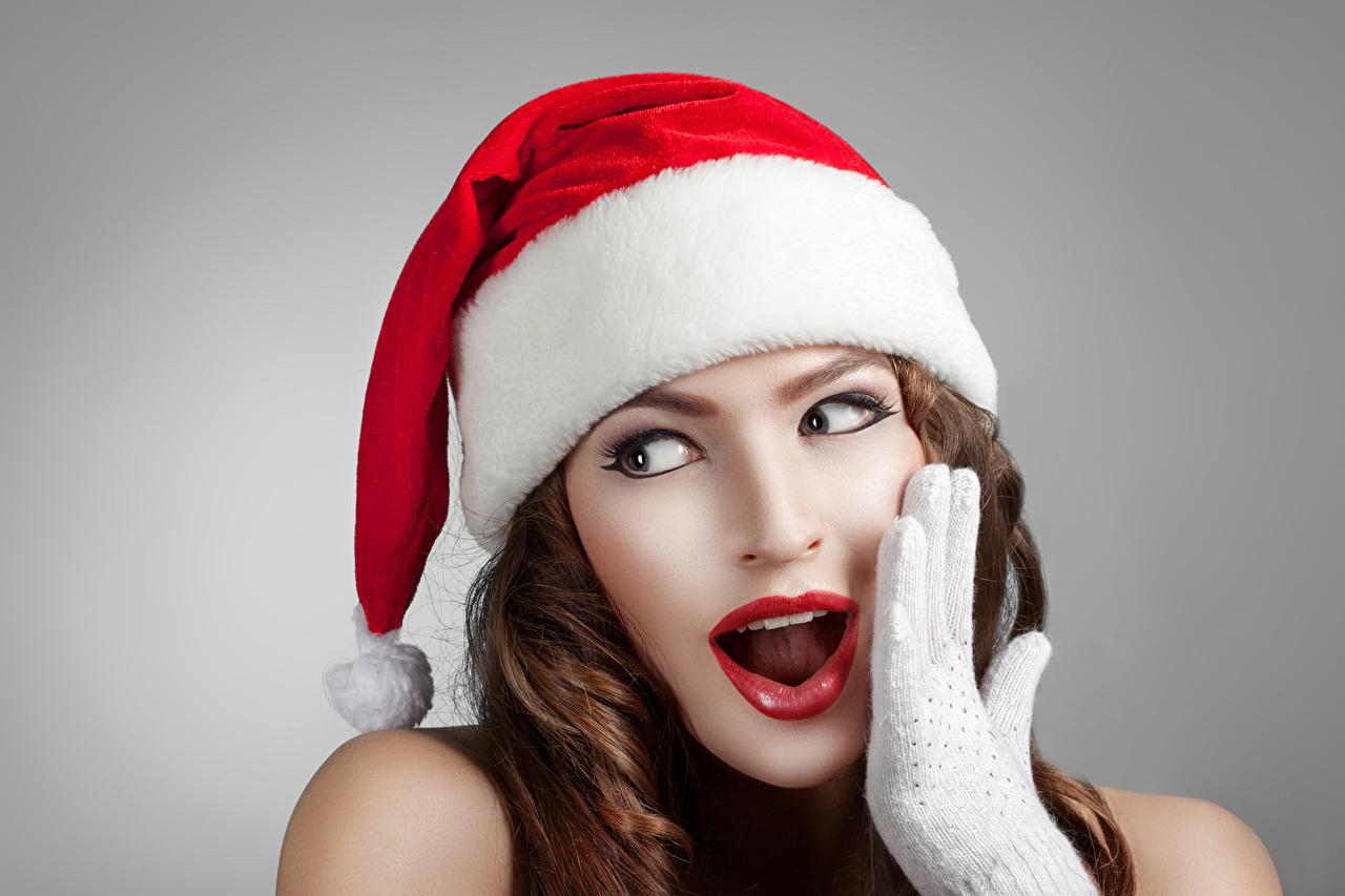 Фото шатенки Новый год Удивление шапка Девушки Руки Взгляд Серый фон Шатенка Рождество удивлен удивлена эмоции изумление Шапки в шапке девушка молодые женщины молодая женщина рука смотрят смотрит сером фоне