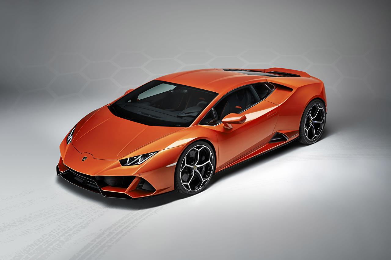 Фотография Ламборгини 2019 Huracan EVO Оранжевый Машины Серый фон Lamborghini Авто Автомобили