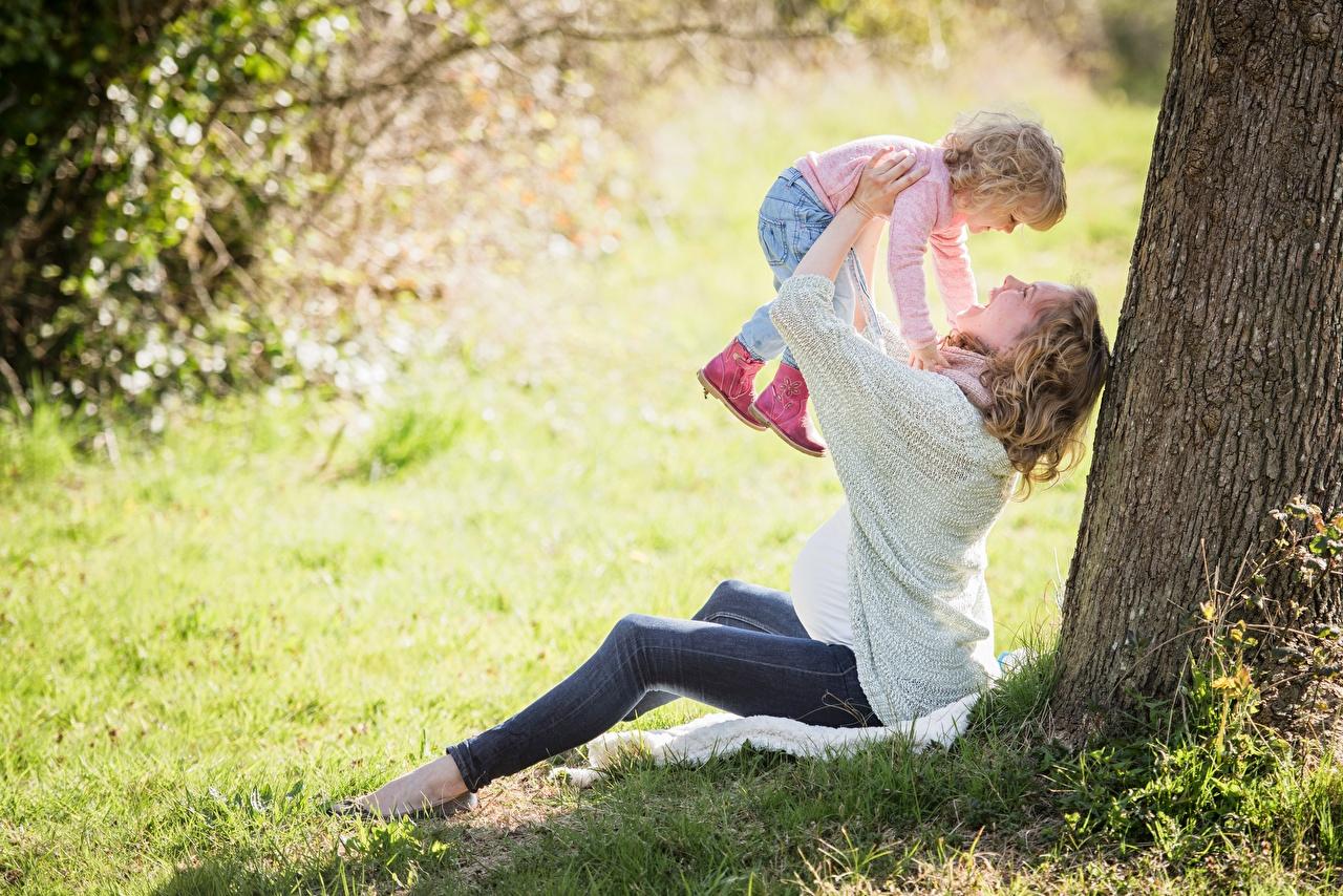 Обои Девочки Блондинка счастливые Ребёнок вдвоем Ствол дерева Сидит Трава Радость счастье Дети 2 Двое сидящие