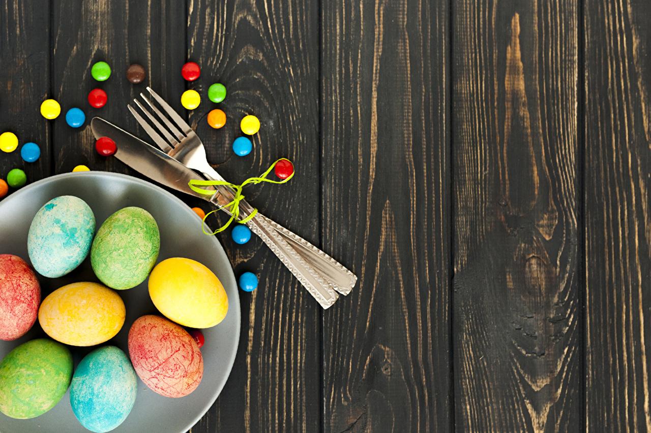 Картинка Пасха Разноцветные Яйца Конфеты Пища Тарелка Вилка столовая Доски Еда Продукты питания