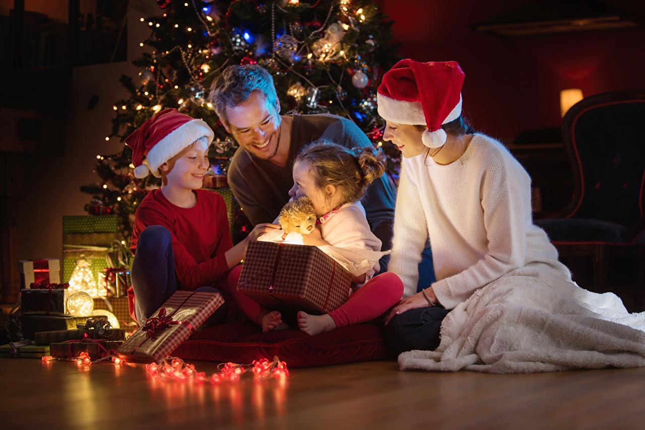 Фотография Девочки Мальчики Новый год Мужчины Улыбка Мать Дети Шапки Подарки Гирлянда Рождество Мама Ребёнок Электрическая гирлянда