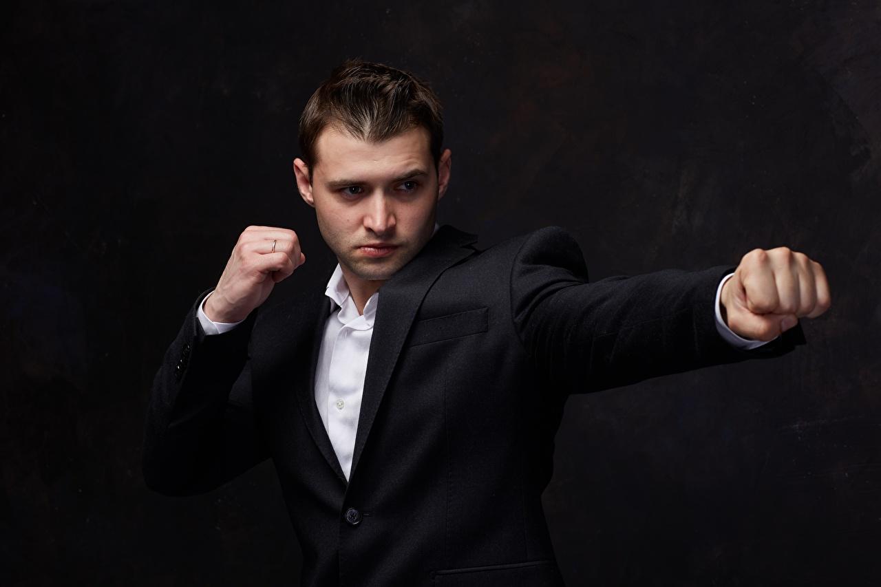 Картинки позирует мужчина рука смотрит Костюм на черном фоне Кулак Ударяет Поза Мужчины Руки Взгляд смотрят костюма костюме Черный фон классический костюм Бьет Удар