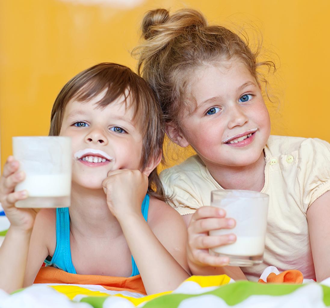 Фото Молоко девочка мальчишки Дети 2 Стакан Взгляд Девочки мальчик Мальчики мальчишка ребёнок две два Двое вдвоем стакана стакане смотрят смотрит