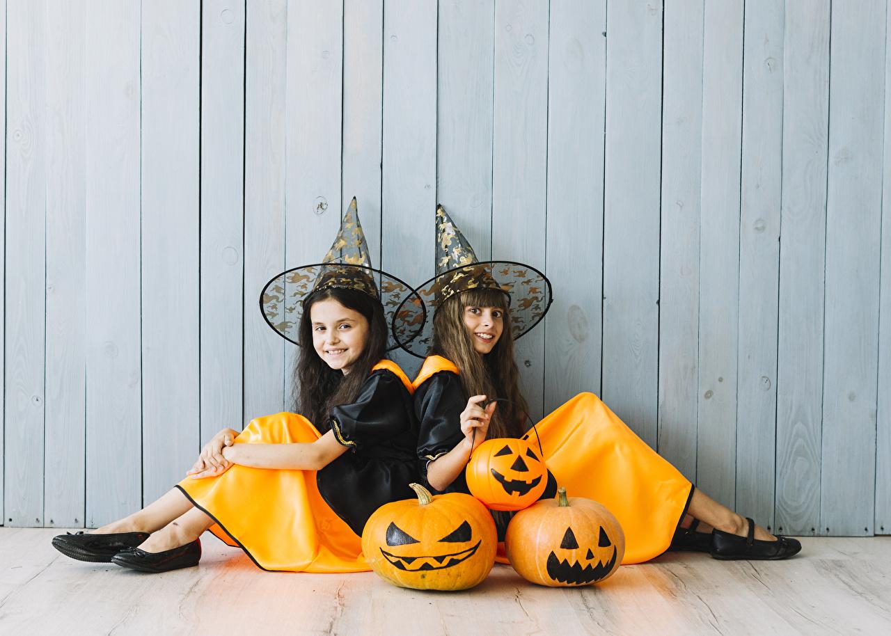 Фотография Девочки Улыбка Дети 2 Тыква шляпы хэллоуин Сидит стенка униформе девочка улыбается ребёнок два две Двое Шляпа шляпе вдвоем Хеллоуин сидя Стена стены стене сидящие Униформа