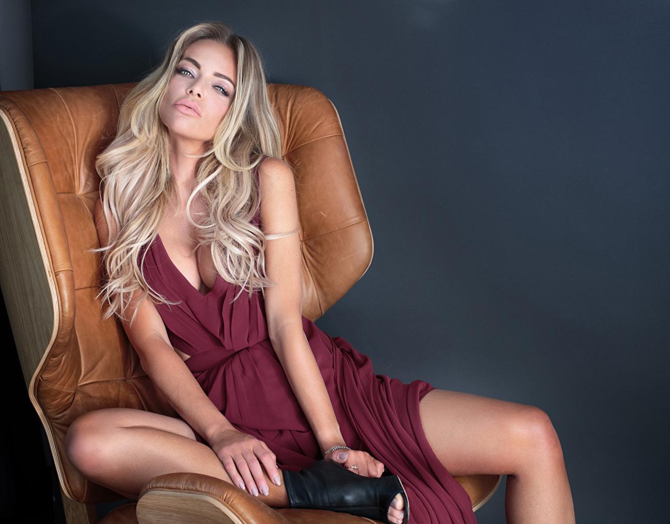Картинка Блондинка молодые женщины сидя Руки Кресло Взгляд сером фоне платья блондинок блондинки девушка Девушки молодая женщина рука Сидит сидящие смотрят смотрит Серый фон Платье