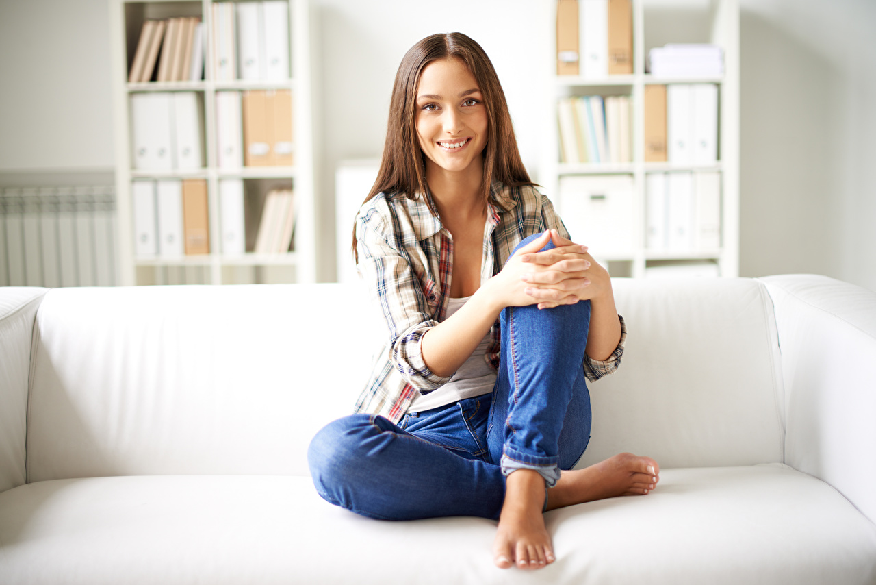 Фото шатенки Улыбка рубашки молодые женщины Ноги Джинсы рука Диван Сидит Шатенка улыбается рубашке Рубашка девушка Девушки молодая женщина ног джинсов сидя Руки диване сидящие