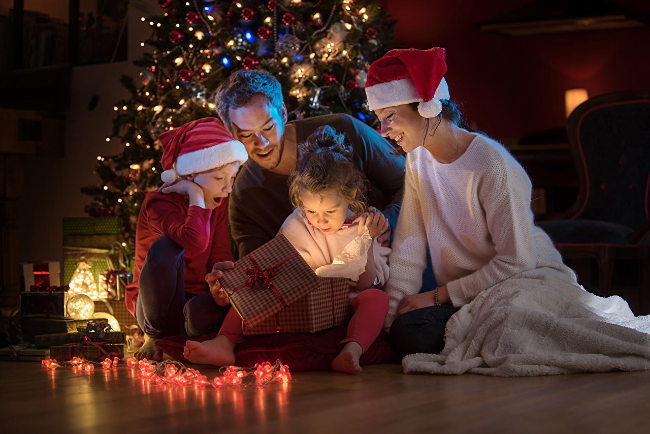 Картинки Девочки Мальчики Рождество Мама Дети Шапки Подарки Гирлянда девочка мальчик мальчишки мальчишка Новый год Мать ребёнок шапка в шапке подарок подарков Электрическая гирлянда