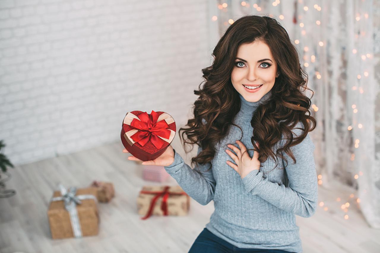 Фотографии Шатенка Новый год Улыбка Девушки свитере Подарки смотрит шатенки Рождество улыбается девушка молодые женщины молодая женщина Свитер подарок свитера подарков Взгляд смотрят