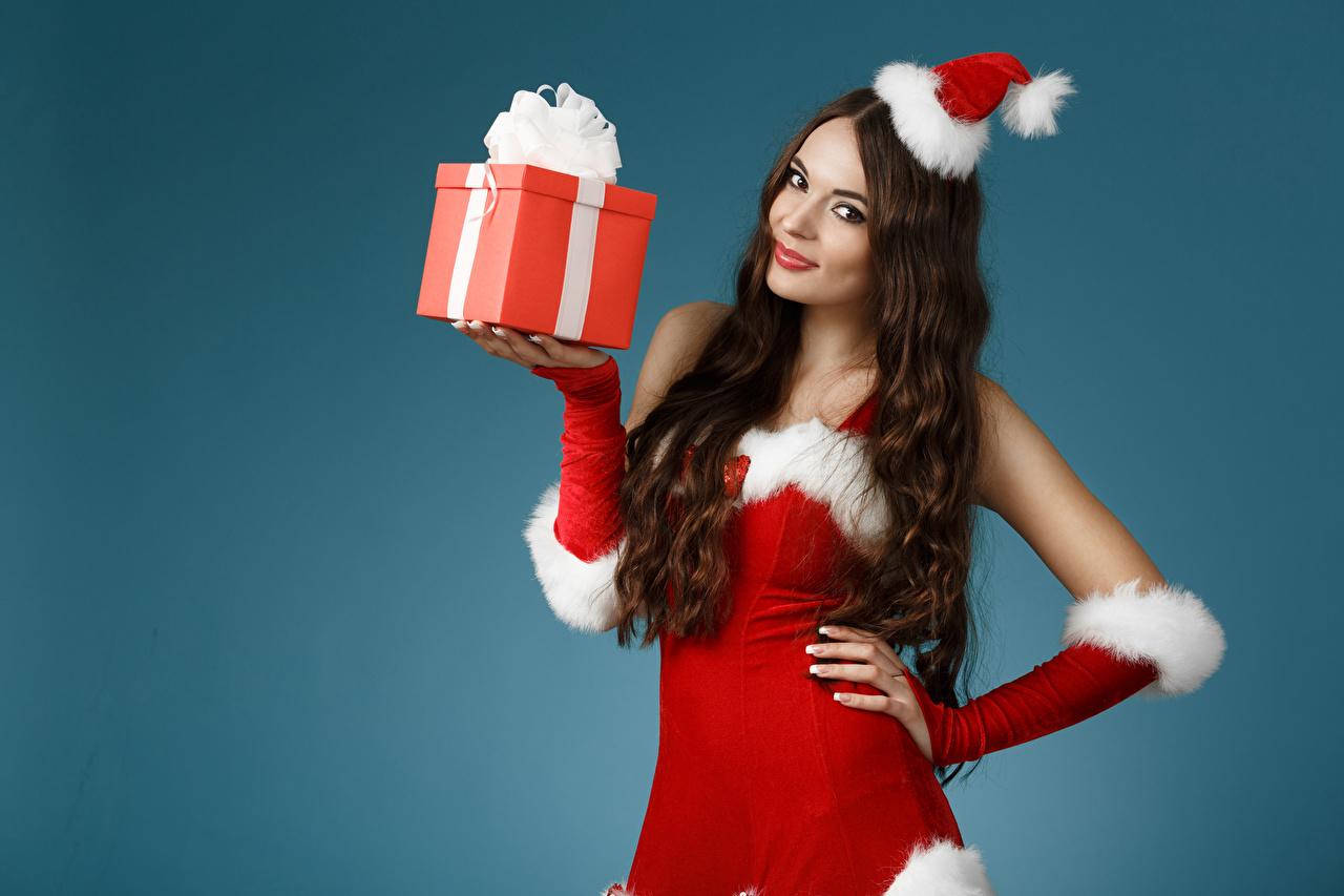 Фотография Шатенка Новый год шапка Девушки Подарки Униформа смотрит Цветной фон шатенки Рождество Шапки в шапке девушка молодые женщины молодая женщина подарок подарков униформе Взгляд смотрят