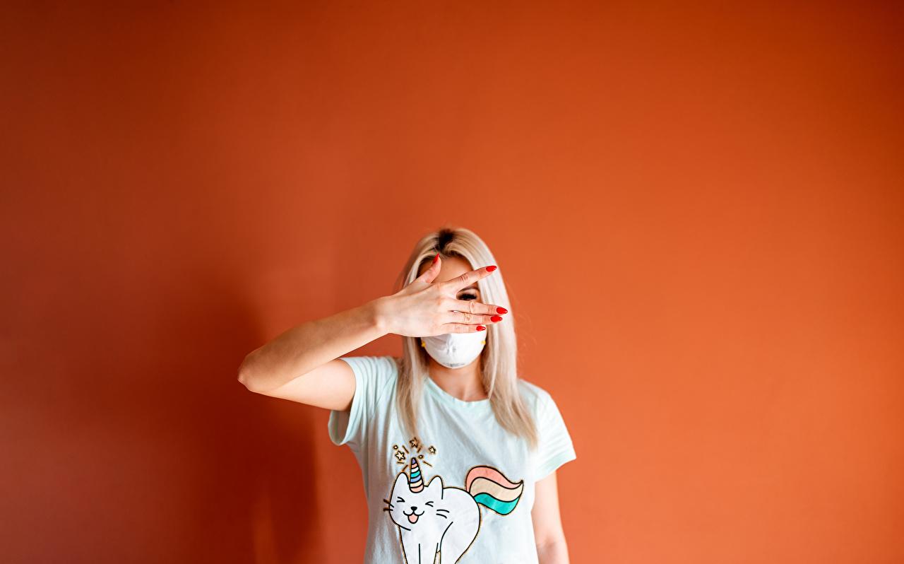 Картинка девушка Цветной фон рука футболке Маски Блондинка жесты Девушки молодая женщина молодые женщины Руки Футболка блондинки блондинок Жест