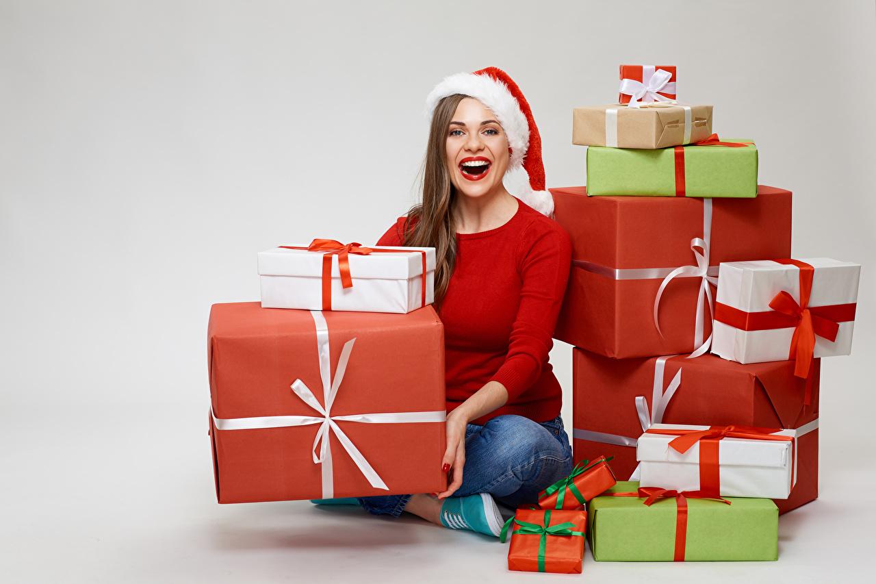 Фотография шатенки Новый год счастливая в шапке Девушки подарок Взгляд сером фоне Шатенка Рождество Радость счастье радостная радостный счастливые счастливый Шапки шапка девушка молодые женщины молодая женщина Подарки подарков смотрят смотрит Серый фон