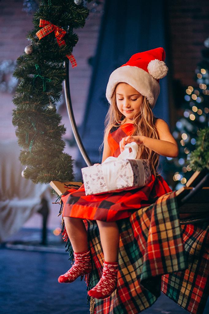 Фотографии Девочки Новый год Дети шапка Подарки сидящие на ветке  для мобильного телефона девочка Рождество ребёнок Шапки в шапке подарок подарков сидя Сидит ветвь ветка Ветки