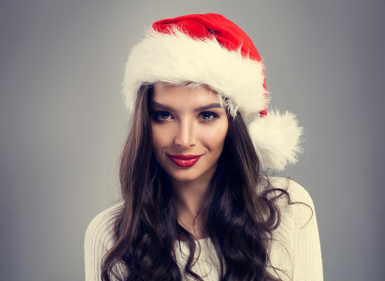 Фотография брюнетки Новый год шапка Волосы Девушки Взгляд сером фоне брюнеток Брюнетка Рождество Шапки волос в шапке девушка молодые женщины молодая женщина смотрят смотрит Серый фон