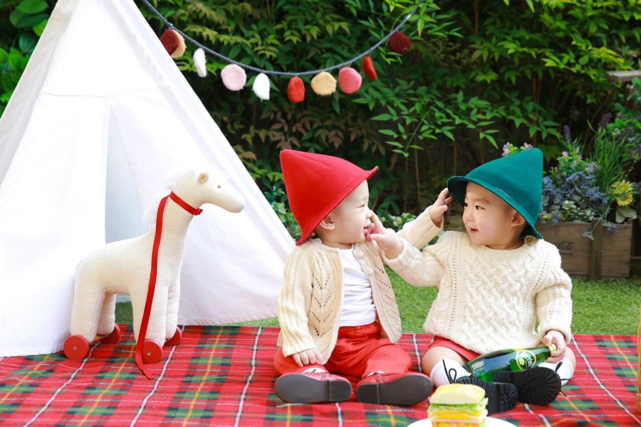 Картинки Мальчики Ребёнок 2 Шапки Свитер Азиаты сидящие Дети Двое вдвоем Сидит