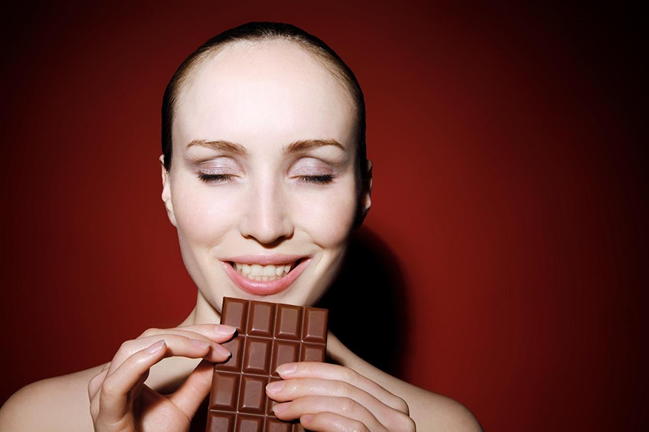 Фотография Улыбка радостная Шоколадная плитка Шоколад лица Девушки Пальцы Цветной фон Радость счастье улыбается радостный счастливые счастливая счастливый шоколадка Лицо девушка молодые женщины молодая женщина