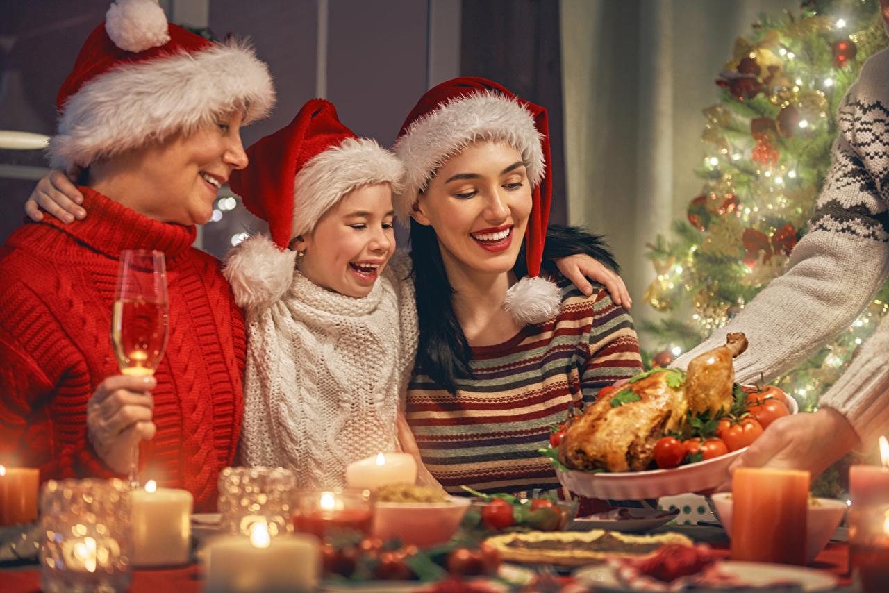 Фотография Девочки Семья Рождество улыбается Мать ребёнок шапка Свечи девочка Новый год Улыбка Мама Дети Шапки в шапке