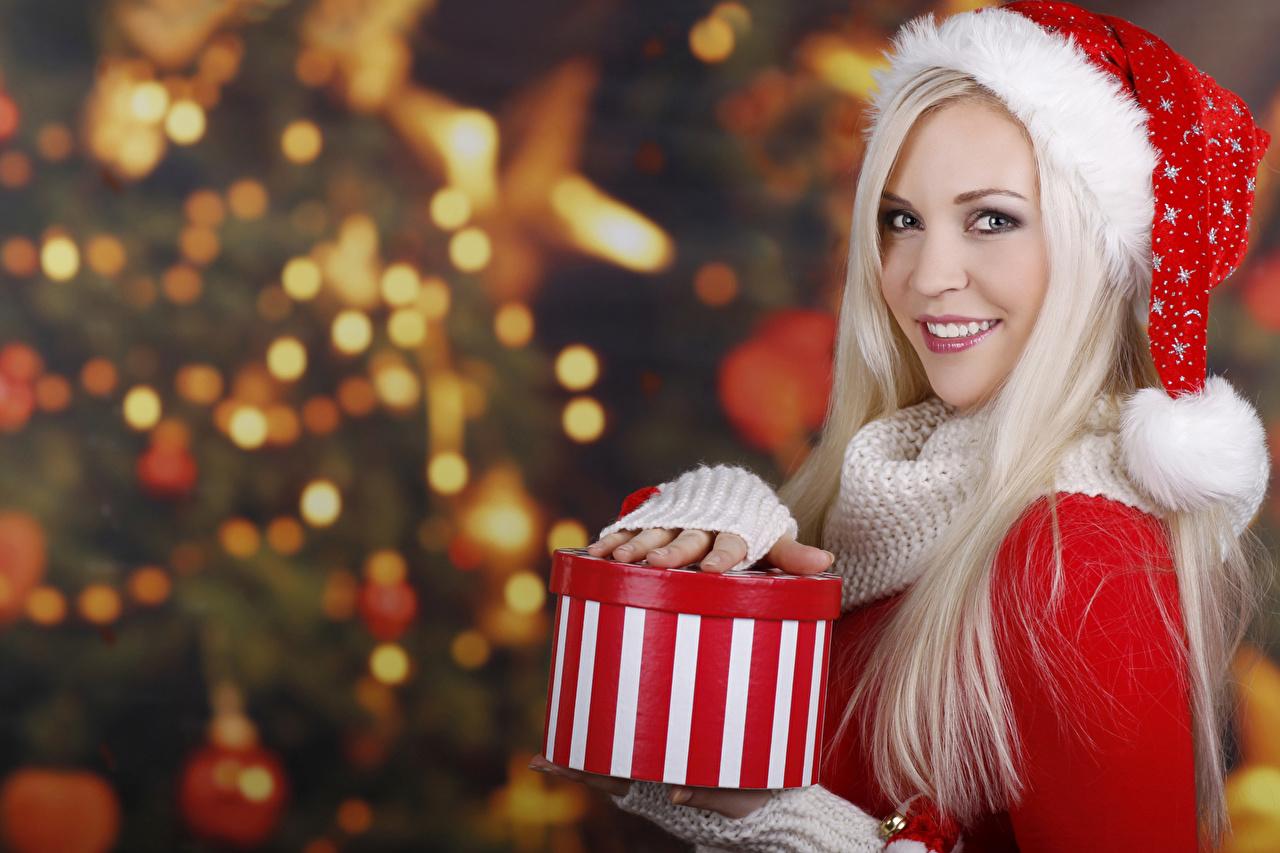 Фотографии Новый год Блондинка Улыбка Шапки Девушки Подарки Взгляд Рождество смотрит