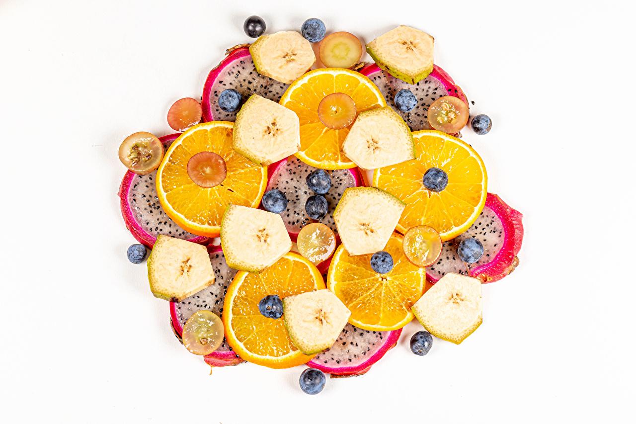 Фотографии Апельсин драконий фрукт Бананы Черника нарезка Продукты питания белом фоне Питайя Еда Пища Нарезанные продукты Белый фон белым фоном