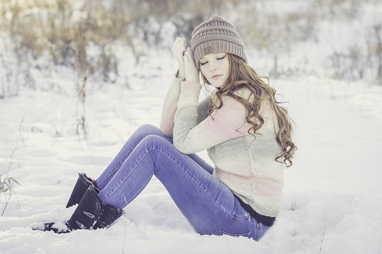 Фотографии Шатенка Шапки зимние Девушки Снег Ноги Свитер Джинсы Сидит Зима сидящие