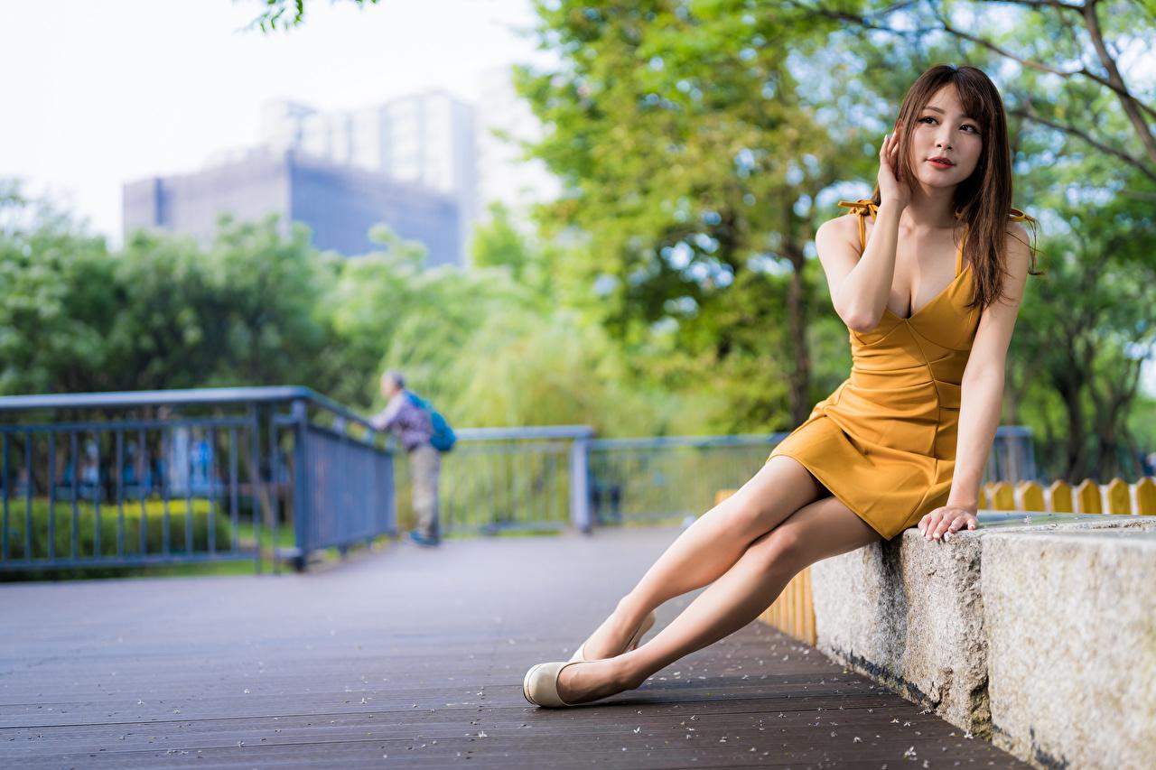 Фото боке девушка Ноги азиатки сидящие смотрит Платье Размытый фон Девушки молодая женщина молодые женщины ног Азиаты азиатка сидя Сидит Взгляд смотрят платья