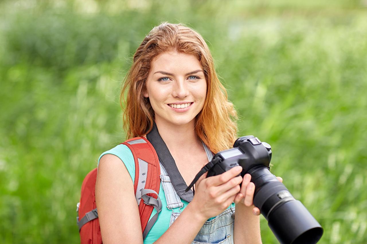 Фото Рыжая фотокамера улыбается Фотограф боке молодая женщина Руки Взгляд рыжие рыжих Фотоаппарат Улыбка Размытый фон девушка Девушки молодые женщины рука смотрит смотрят