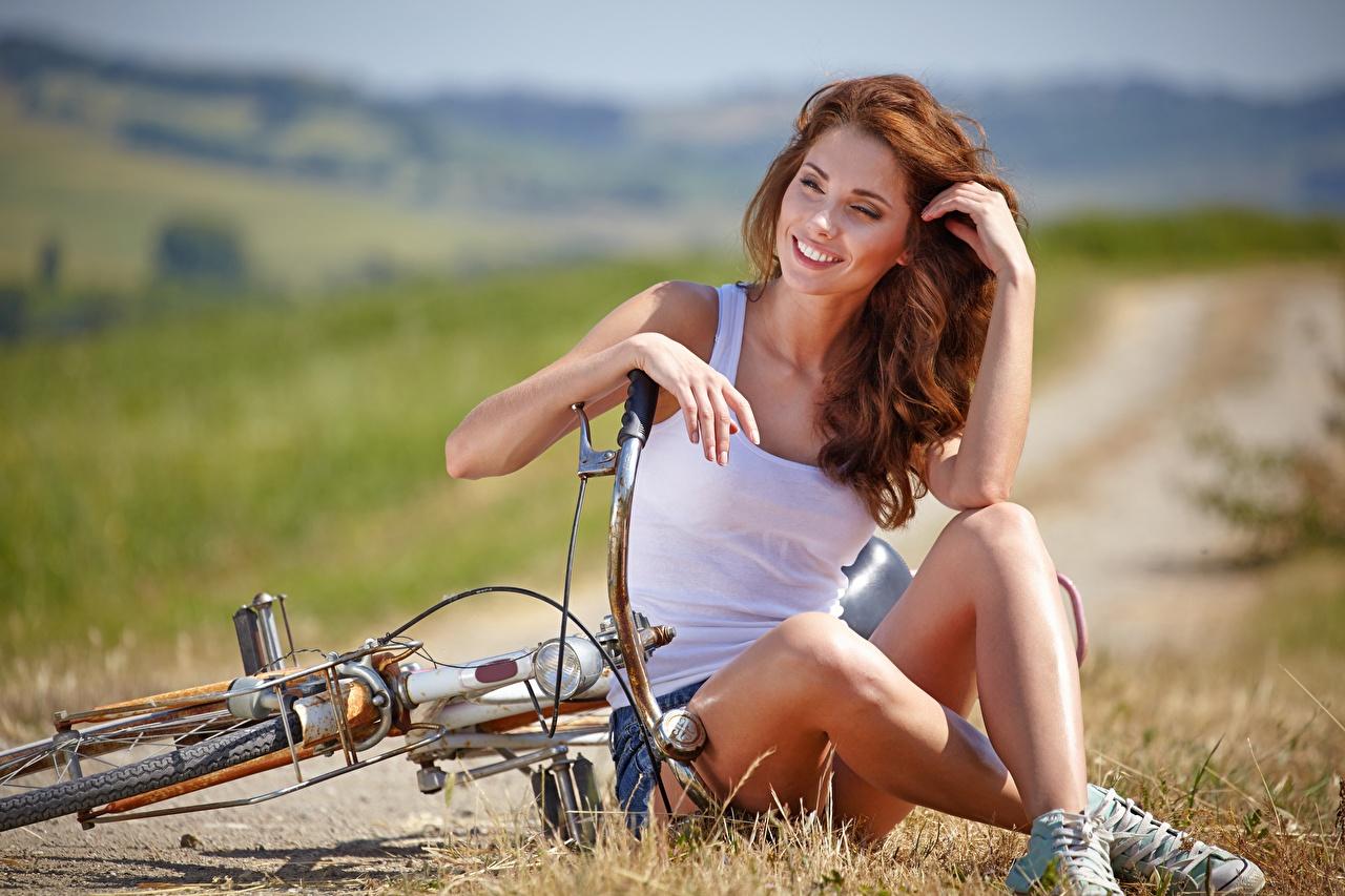 Фото молодые женщины Сидит рыжих Ноги Трава Размытый фон рука Майка Улыбка Izabela Magier Велосипед девушка Девушки молодая женщина сидя сидящие рыжие Рыжая ног траве боке Руки майки майке улыбается велосипеды велосипеде