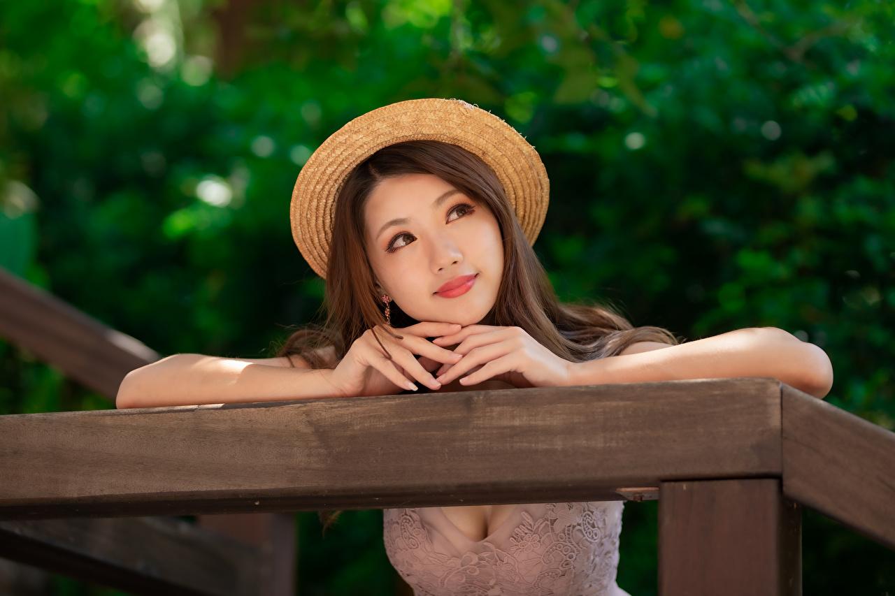 Фото Размытый фон вырез на платье шляпе Девушки азиатка рука Взгляд платья боке Декольте Шляпа шляпы девушка молодые женщины молодая женщина Азиаты азиатки Руки смотрят смотрит Платье