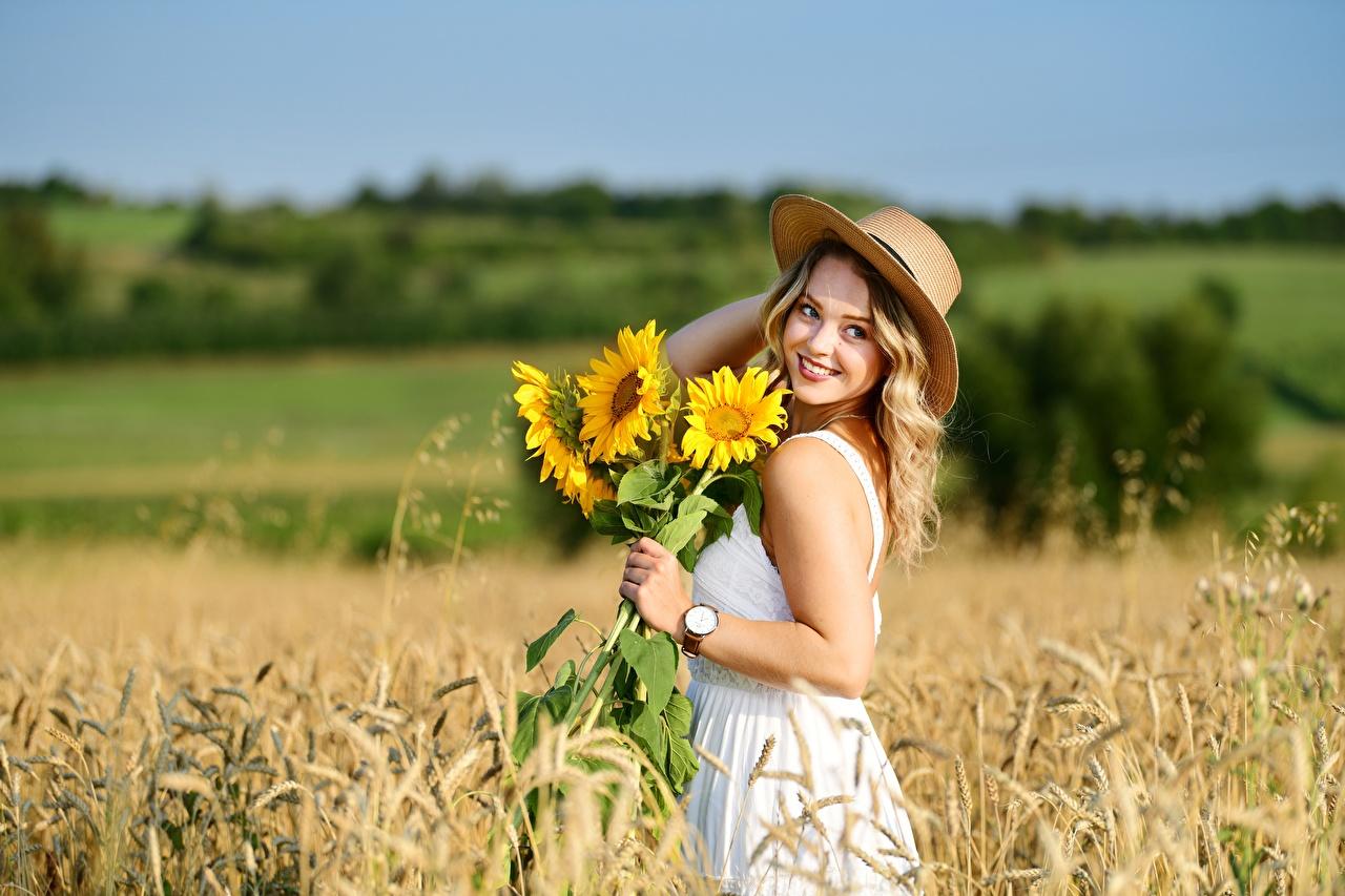 Картинки блондинок улыбается Размытый фон Шляпа Девушки Природа Пшеница Поля Подсолнухи Платье Блондинка блондинки Улыбка боке шляпе шляпы девушка молодые женщины молодая женщина Подсолнечник платья