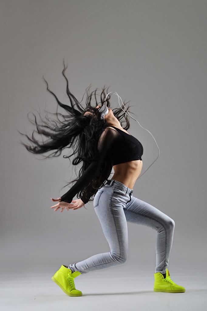 Фотографии Шатенка Наушники Танцы Девушки Джинсы Серый фон Танцует