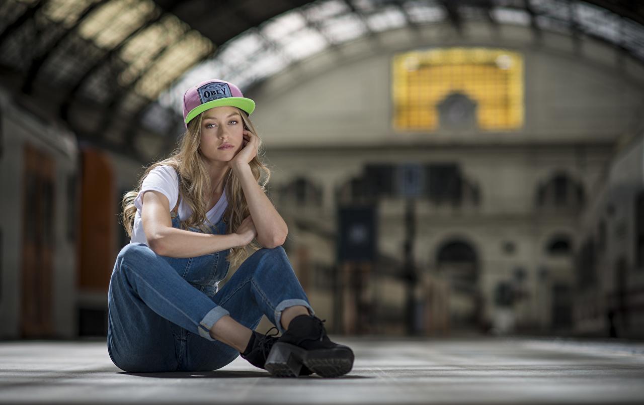 Картинка боке позирует Девушки Джинсы сидя кепке Взгляд Размытый фон Поза девушка молодые женщины молодая женщина джинсов Сидит сидящие Кепка кепкой смотрит смотрят Бейсболка