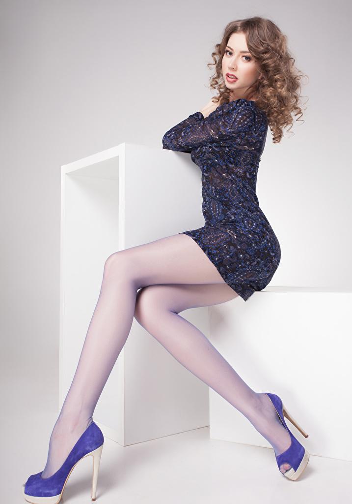 Картинка шатенки Девушки ног Сидит Взгляд Серый фон платья туфлях  для мобильного телефона Шатенка девушка молодые женщины молодая женщина Ноги сидя сидящие смотрят смотрит сером фоне Платье Туфли туфель