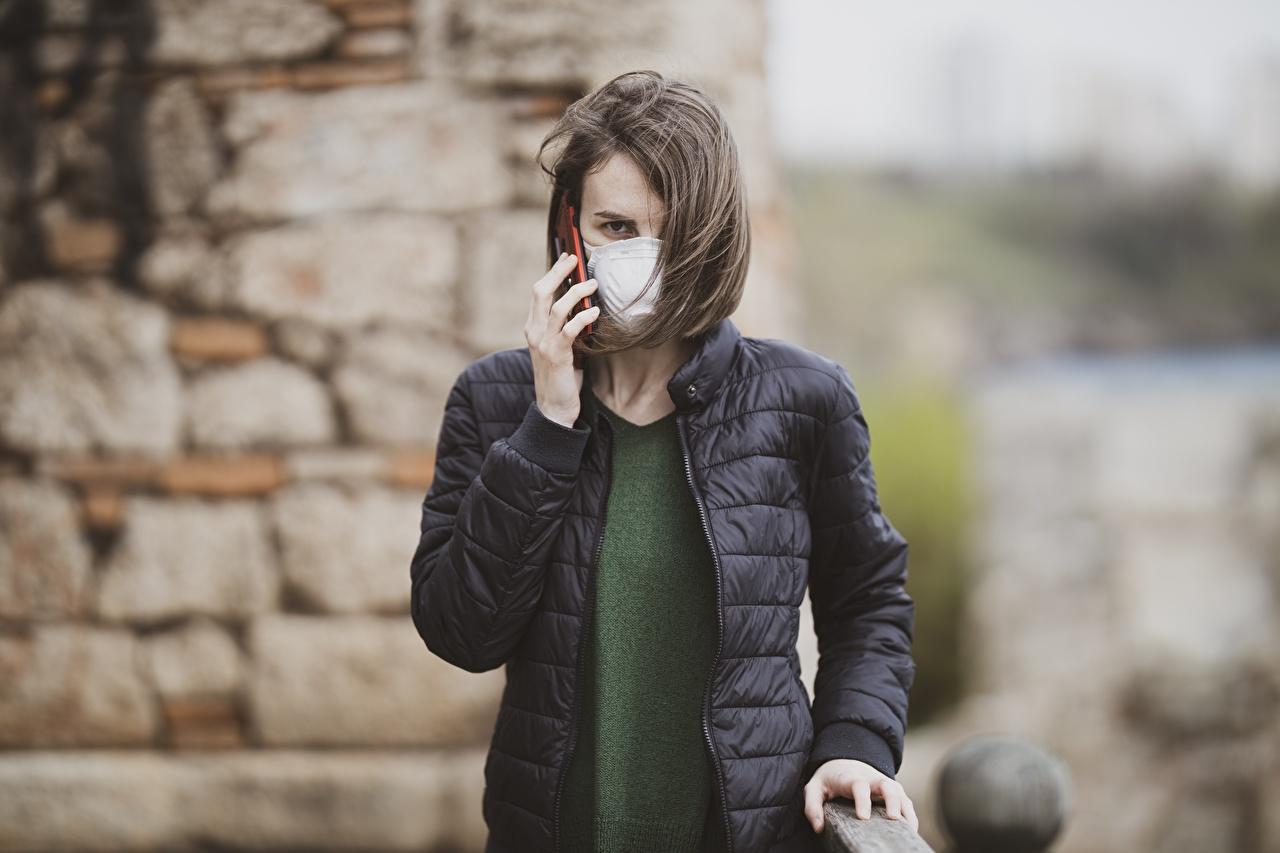 Фото Коронавирус брюнетки Размытый фон куртки девушка Руки Маски смотрят Брюнетка брюнеток боке куртке Куртка куртках Девушки молодая женщина молодые женщины рука Взгляд смотрит