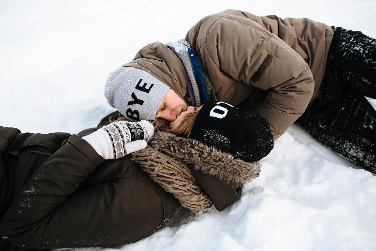 Картинка Мужчины Влюбленные пары Поцелуй 2 Зима Шапки Любовь Девушки Снег любовники Двое вдвоем зимние
