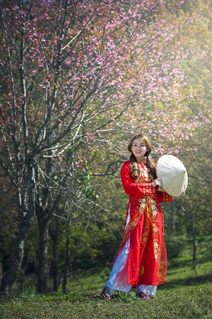 Фото Шатенка Весна Шляпа молодые женщины Азиаты траве Цветущие деревья шатенки шляпы шляпе Девушки девушка весенние молодая женщина азиатки Трава
