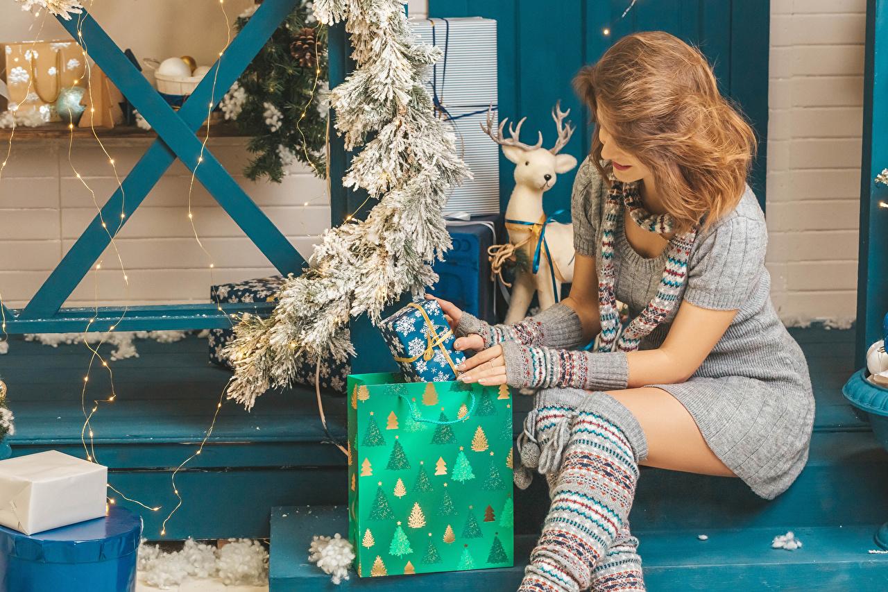 Картинка Шатенка Новый год Шарф девушка подарков сидя Ветки Гирлянда платья шатенки Рождество шарфе шарфом Девушки молодая женщина молодые женщины подарок Подарки Сидит ветвь ветка сидящие на ветке Электрическая гирлянда Платье