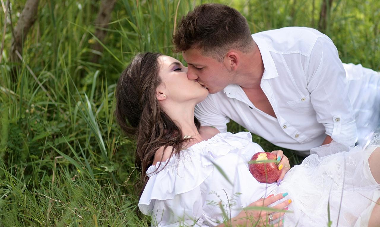 Картинка Девушки шатенки мужчина Влюбленные пары Поцелуй 2 Свидание Яблоки траве девушка молодые женщины молодая женщина Шатенка Мужчины любовники целует поцелуи целование целоваться две два Двое вдвоем свидании Трава