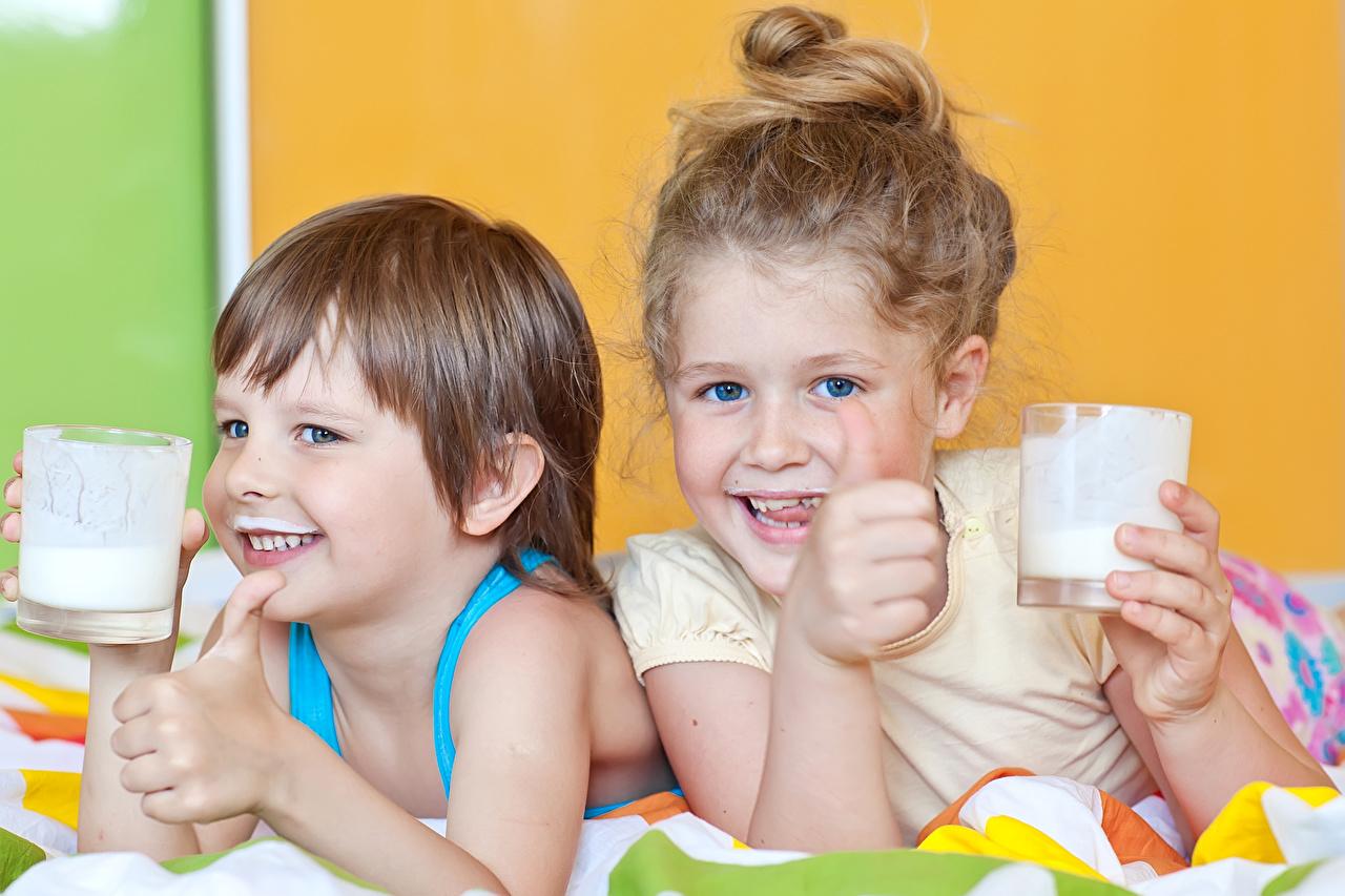 Картинка Молоко Девочки мальчик улыбается Ребёнок вдвоем стакане Пальцы девочка Мальчики мальчишки мальчишка Улыбка Дети 2 Двое Стакан стакана