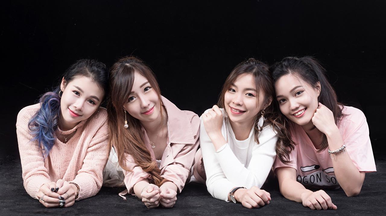 Фото Улыбка лежа Четыре 4 Девушки Азиаты Взгляд на черном фоне улыбается Лежит лежат лежачие девушка молодая женщина молодые женщины азиатки азиатка смотрит смотрят Черный фон