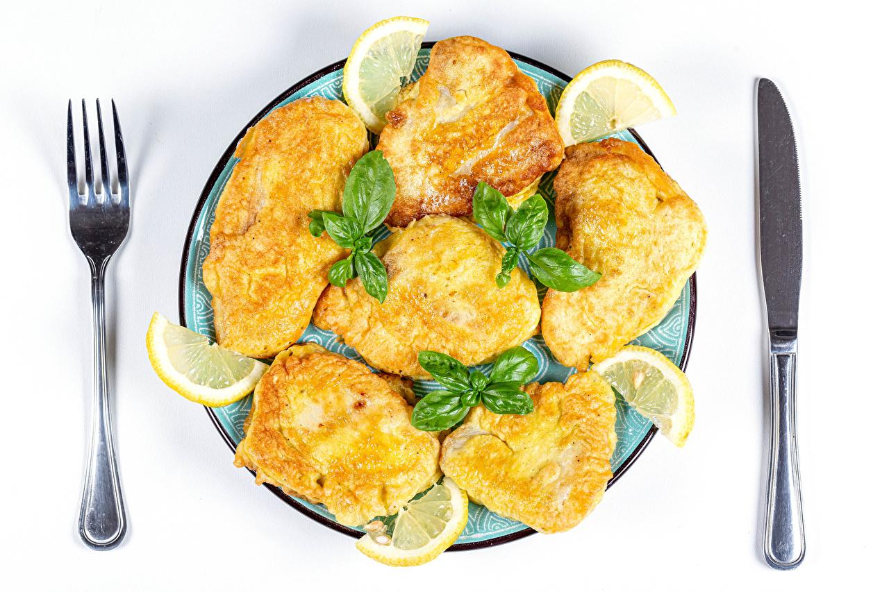 Фотография Нож fish in dough Рыба Лимоны вилки тарелке Продукты питания белым фоном ножик Еда Пища Тарелка Вилка столовая Белый фон белом фоне